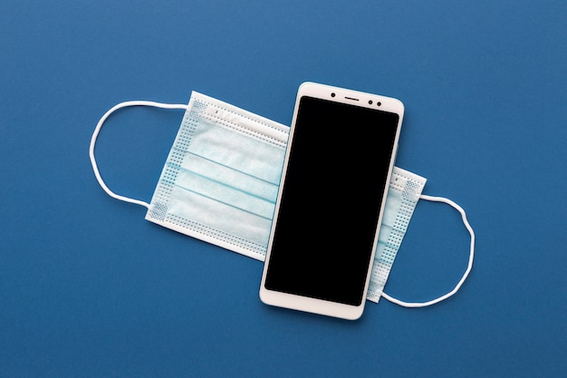 Flat lay of smartphone with medical mask