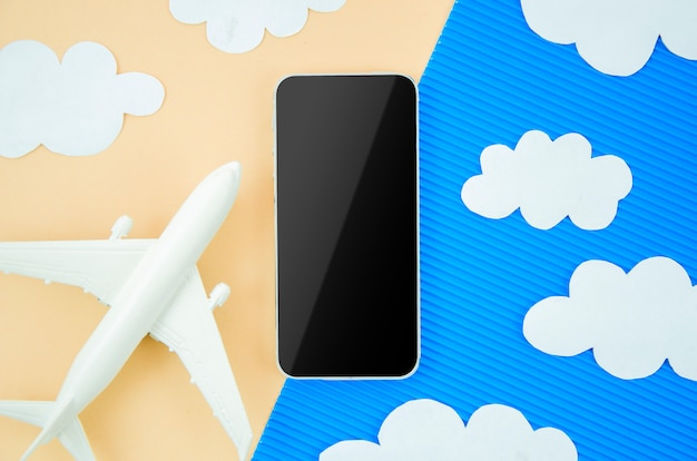 Flat lay smartphone with a model plane and paper cut clouds