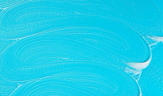 青色の背景にフラットレイアウト石鹸の泡