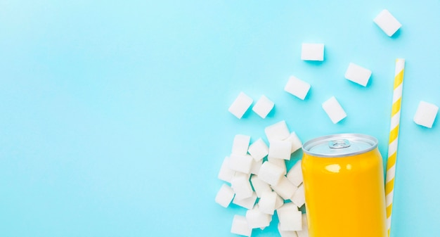 Flat lay of soft drink can with sugar cubes and straw
