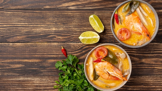 Flat lay soups in bowls with shrimp on wooden background with copy space