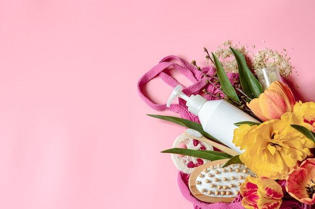 Flat lay spa composition with flowers and bath accessories in a string bag.
