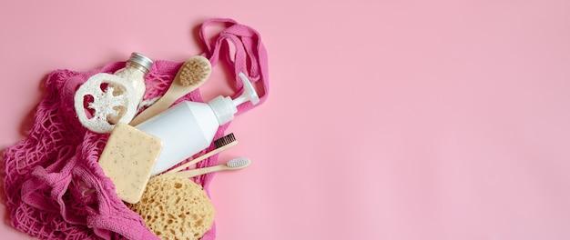 ストリングバッグに個人用衛生用品とバスアクセサリーを入れたフラットレイスパコンポジション。