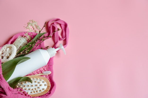 Flat lay spa composition with personal hygiene items and bath accessories in a string bag.