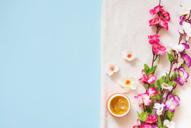 Flat lay of spa cream and color flowers on white towel on blue background
