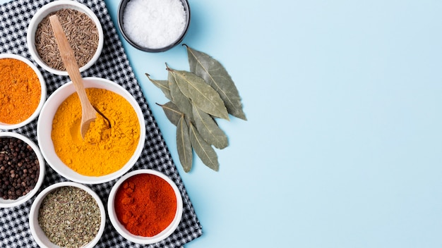 Flat lay spices and leaves on blue background