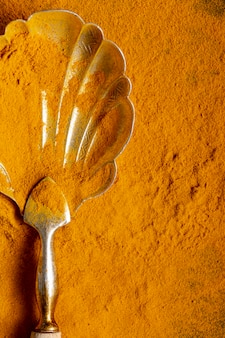 Flat lay of spoon with turmeric with copy space