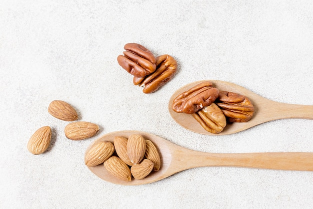 Flat lay of spoons with walnuts and almonds