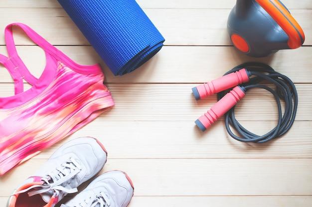 木製の背景にフラットレイアウトスポーツとフィットネスアイテム。健康的な食事療法の概念