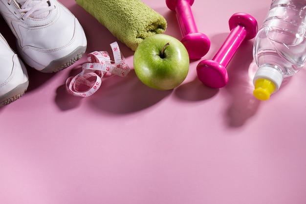 フラットレイスポーツの概念明るいピンクの背景に健康的なライフ機器。コピースペースとクローズアップ。