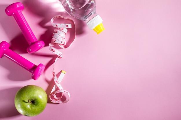 Flat lay sport concept здоровое питание на светло-розовом фоне. макрофотография с копией пространства.