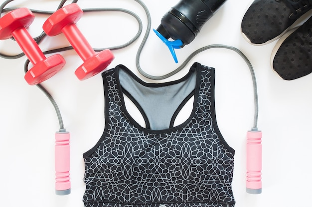 Flat lay of sport equipments with sport bra on white background, overhead view, top view