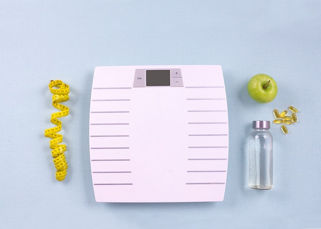 Flat lay sport items, scales, water, apple, omega 3 on blue background. weight loss concept. top view.