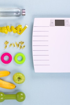 Flat lay sport items, scales, water, apple, omega 3 on blue wall. weight loss concept. top view.