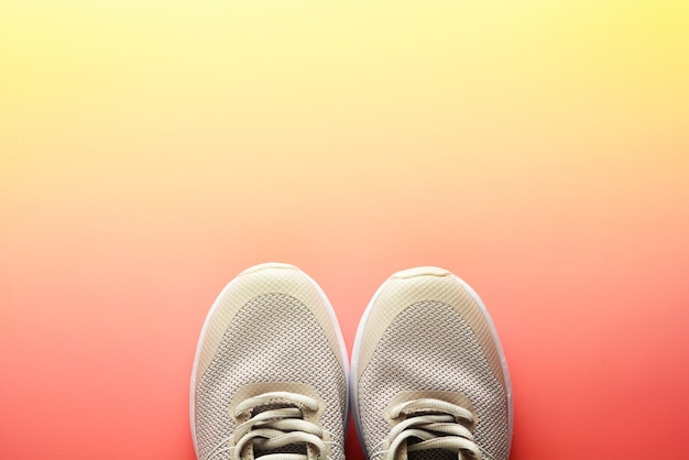 Flat lay of sport shoes on a pink background running workout fitness