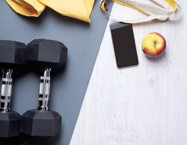 Flat lay of the sports concept - gray mat, yellow towel, telephone, measuring tape, two dumbbells and an apple