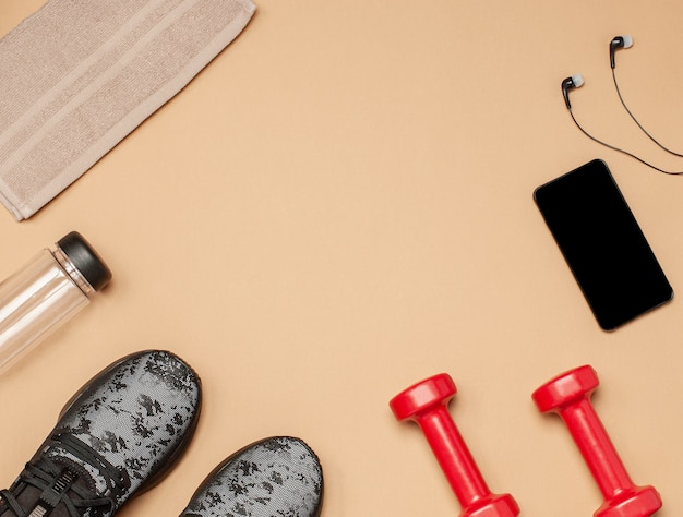 Flat lay of sports equipment for fitness on a beige surface
