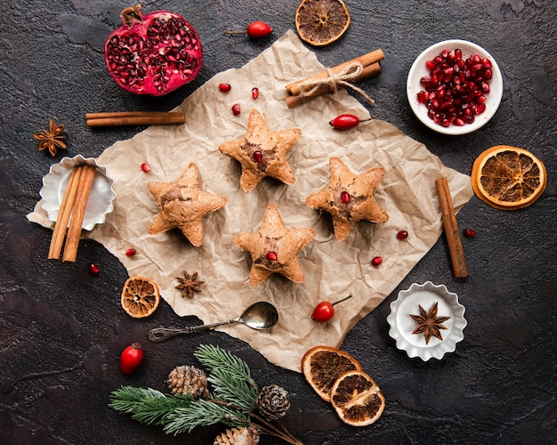 Flat lay of star-shaped cookies with pomegranate and cinnamon