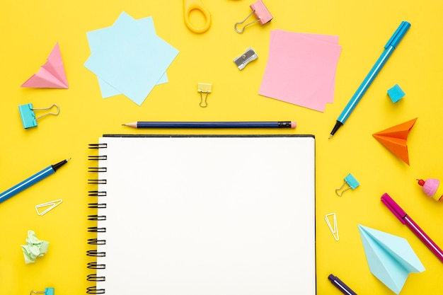 Плоская планировка канцелярских товаров на желтом фоне с пустой записной книжкой