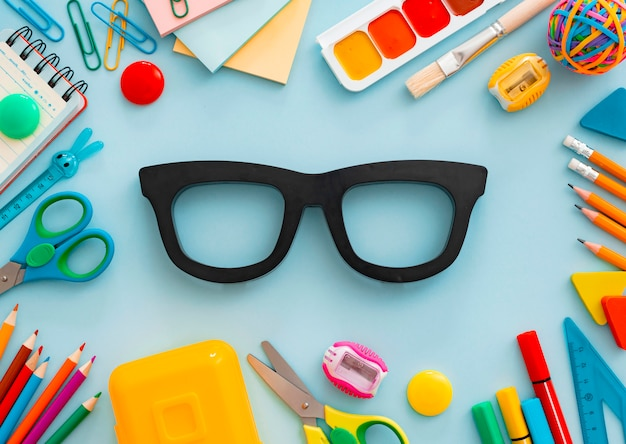 Flat-lay stationery chalk board eyeglass frames on white table. concept of returning to school, training, office