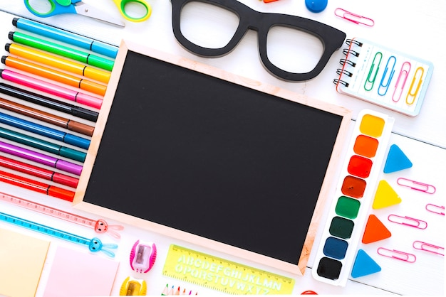 Flat-lay stationery chalk board eyeglass frames on white of the table