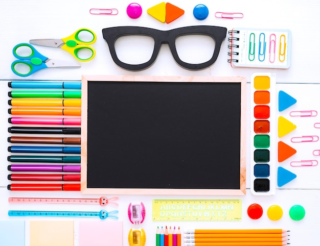 Flat-lay stationery chalk board eyeglass frames on white