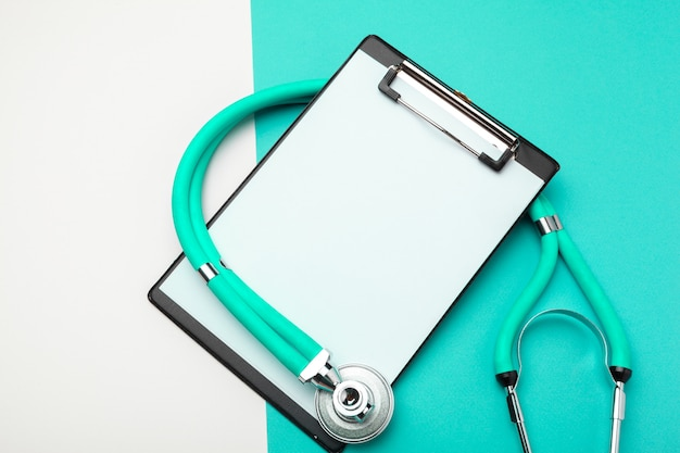Flat lay of stethoscope and blank clipboard pad