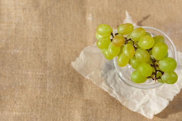 Плоская планировка, натюрморт и фото еды. блюдо с гроздью ягод зеленого винограда стоит на мешковине