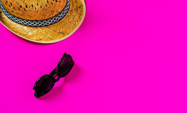 Flat lay, straw hat and sunglasses on a pink surface