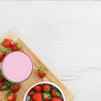 Flat lay of strawberry smoothie with fruits