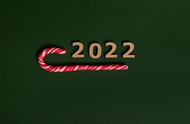 木製の数字2022と甘い縞模様の白と赤のクリスマスロリポップ、甘いキャンディケインのフラットレイスタジオショット、広告のためのスペースで新年とクリスマスの伝統的なイベントを象徴しています