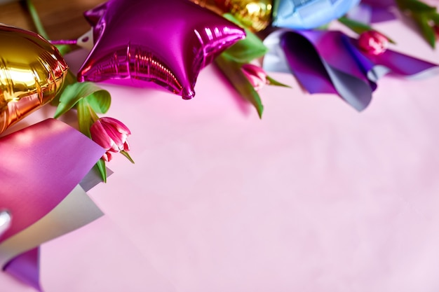 Flat lay style of color balloons with tulips floral decoration on pink background. copy space for text.