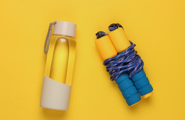 健康的なライフスタイル、スポーツ、フィットネスのフラットレイスタイルのコンセプト。水のボトル、黄色の背景に縄跳び。上面図