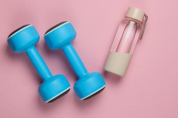 健康的なライフスタイル、スポーツ、フィットネスのフラットレイスタイルのコンセプト。ダンベル、ピンクのパステルカラーの背景に水のボトル。上面図