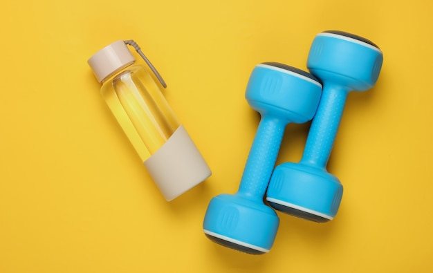 健康的なライフスタイル、スポーツ、フィットネスのフラットレイスタイルのコンセプト。ダンベル、黄色の背景に水のボトル。上面図