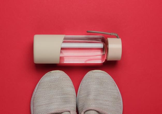 健康的なライフスタイル、スポーツ、フィットネスのフラットレイスタイルのコンセプト。ランニング用のスポーツシューズ、赤い背景に水のボトル。上面図