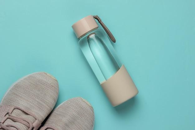 健康的なライフスタイル、スポーツ、フィットネスのフラットレイスタイルのコンセプト。ランニング用のスポーツシューズ、青いパステルカラーの背景に水のボトル。上面図
