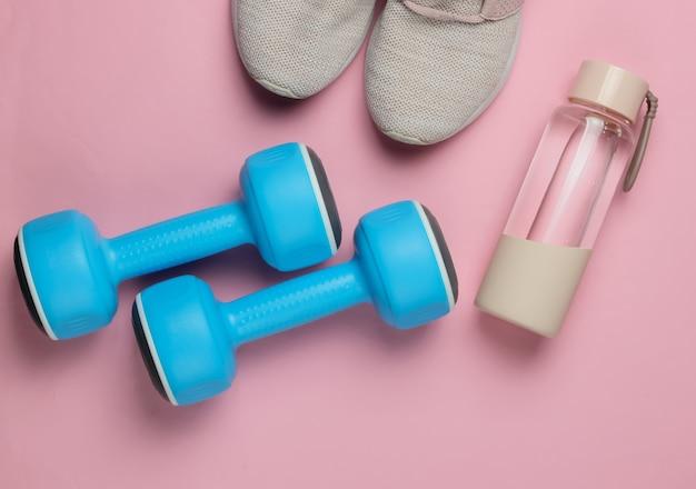 健康的なライフスタイル、スポーツ、フィットネスのフラットレイスタイルのコンセプト。ランニング用のスポーツシューズ、ダンベル、ピンクのパステルカラーの背景に水のボトル。上面図