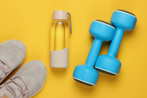 健康的なライフスタイル、スポーツ、フィットネスのフラットレイスタイルのコンセプト。ランニング用のスポーツシューズ、ダンベル、黄色の背景に水のボトル。上面図