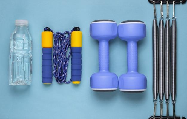 フラットレイスタイルのフィットネスコンセプト。ダンベル、縄跳び、ボトル入り飲料水、エキスパンダー。青のスポーツ用品