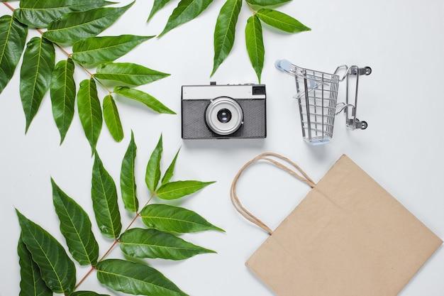 Flat lay style shopaholic still life. shopping cart, eco paper bag, retro camera on white background among green leaves.