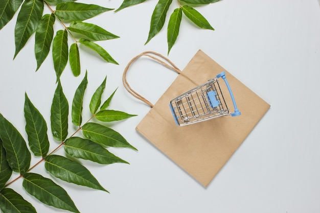 Flat lay style shopaholic still life. shopping cart, eco paper bag on white background among green leaves.