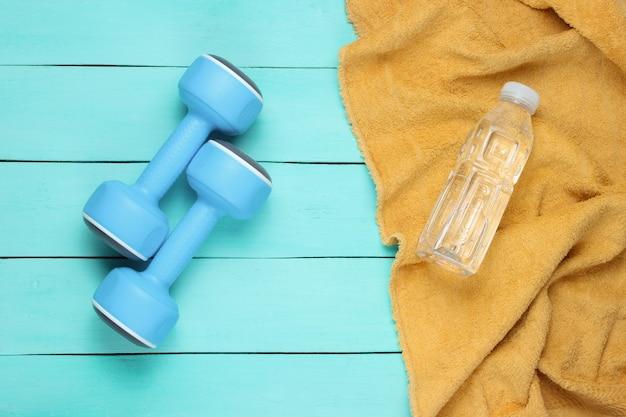 フラットレイスタイルのスポーツコンセプト。ダンベル、青い木製の背景にタオルと水のボトル。上面図