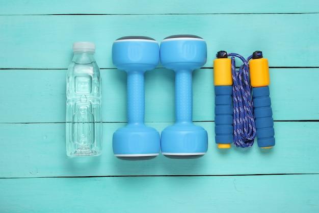 フラットレイスタイルのスポーツコンセプト。ダンベル、縄跳び、ボトル入り飲料水。青い木製の背景にスポーツ用品。
