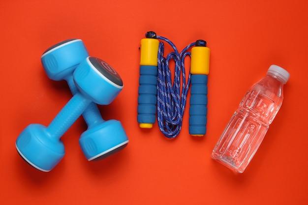 フラットレイスタイルのスポーツコンセプト。ダンベル、縄跳び、ボトル入り飲料水。オレンジ色の背景にスポーツ用品。上面図