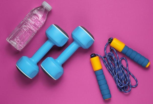 フラットレイスタイルのスポーツコンセプト。ダンベル、縄跳び、ボトル入り飲料水。ピンクのスポーツ用品