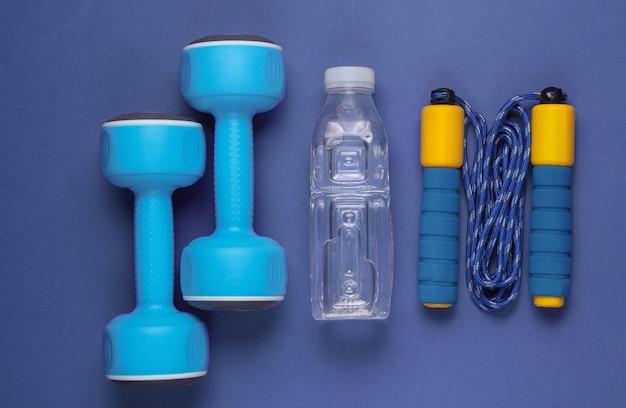 フラットレイスタイルのスポーツコンセプト。ダンベル、縄跳び、ボトル入り飲料水。紫のスポーツ用品