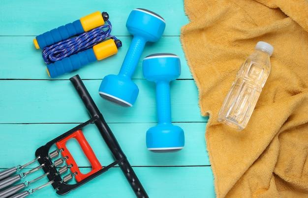 フラットレイスタイルのスポーツコンセプト。青い木製の背景にダンベル、縄跳び、タオルと水のボトル、その他のスポーツ用品。
