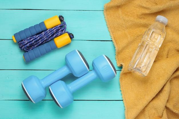 フラットレイスタイルのスポーツコンセプト。ダンベル、縄跳び、ボトル入り飲料水とタオル。青い木製の背景にスポーツ用品。上面図