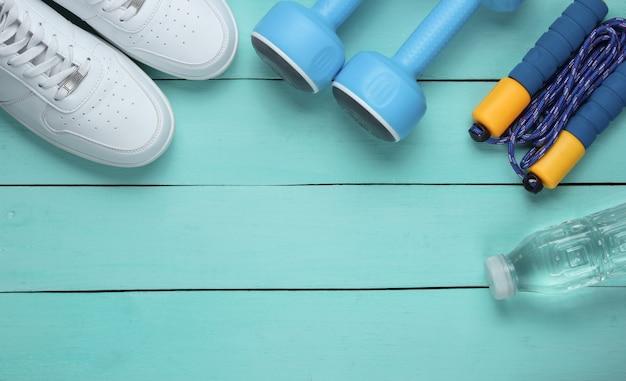 フラットレイスタイルのスポーツコンセプト。ダンベル、スニーカー、縄跳び、ボトル入り飲料水。青い木製の背景にスポーツ用品。